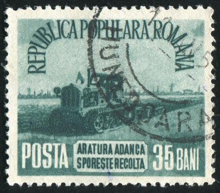 ROMANIA - CIRCA 1953: stamp printed by Romania, shows Tractor in field, circa 1953 photo