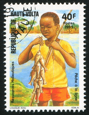 BURKINA FASO - CIRCA 1983: stamp printed by Burkina Faso, shows Boy fishing, circa 1983 photo