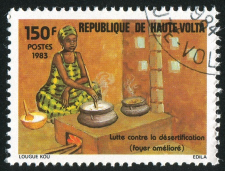 steam mouth: BURKINA FASO - CIRCA 1983: stamp printed by Burkina Faso, shows Woman cooking, circa 1983