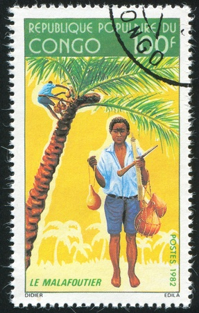 CONGO CIRCA 1982: stamp printed by Congo, shows Boy Gathering Coconuts, circa 1982 photo