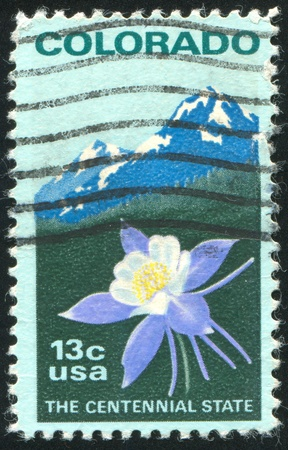 UNITED STATES - CIRCA 1977 : stamp printed by United States of America, shows Colombine flower and Rocky Mountain, circa 1977 photo