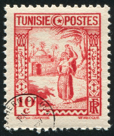 road shoulder: TUNISIA - CIRCA 1936: stamp printed by Tunisia, shows Arab Woman Carrying Water, circa 1936