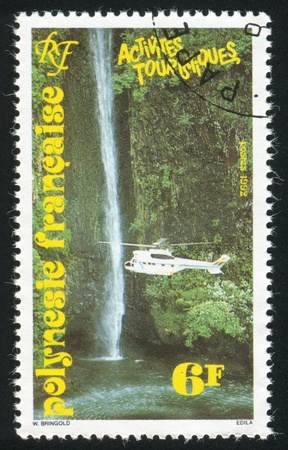 FRENCH POLYNESIA CIRCA 1992: stamp printed by French Polynesia, shows Waterfalls, helicopter, circa 1992 photo