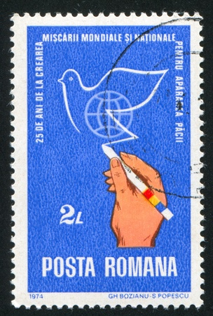 peace stamp: ROMANIA - CIRCA 1974: stamp printed by Romania, shows hand drawing peace dove, circa 1974 Stock Photo