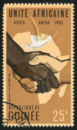 GUINEA CIRCA 1963: stamp printed by Guinea, shows Handshake, Map and Dove, circa 1963 photo