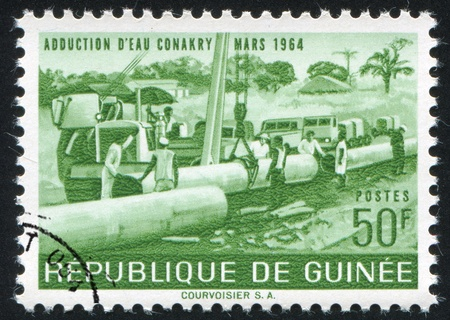 GUINEA CIRCA 1964: stamp printed by Guinea, shows Laying pipe, circa 1964 photo