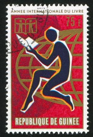 GUINEA CIRCA 1972: stamp printed by Guinea, shows Man reading and globe, circa 1972 photo