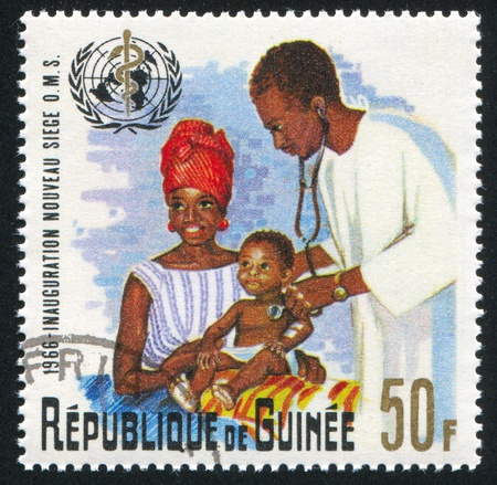 GUINEA CIRCA 1967: stamp printed by Guinea, shows Physician examining Infant, circa 1967 Stock Photo - 11371192