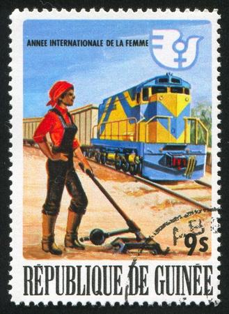GUINEA CIRCA 1976: stamp printed by Guinea, shows Woman railroad shunter and train, circa 1976 Stock Photo - 11448248
