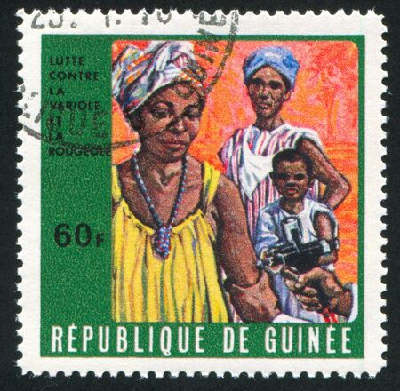 GUINEA CIRCA 1970: stamp printed by Guinea, shows Mother receiving vaccination, circa 1970 photo