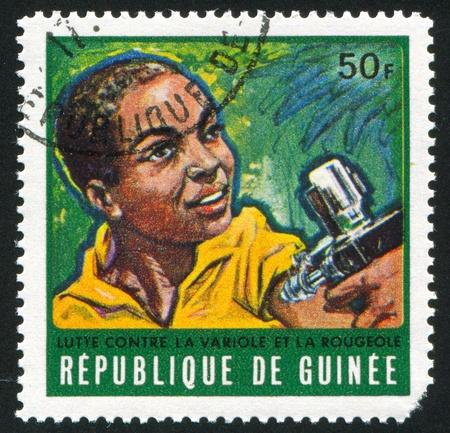GUINEA CIRCA 1970: stamp printed by Guinea, shows Boy receiving vaccination, circa 1970 photo