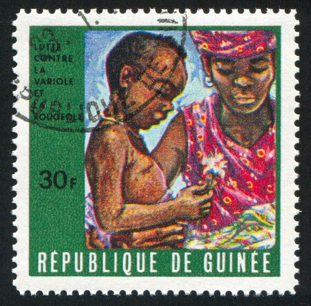 GUINEA CIRCA 1970: stamp printed by Guinea, shows Mother and Sick Child, circa 1970 photo