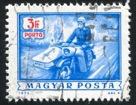 HUNGARY - CIRCA 1973: stamp printed by Hungary, shows mailman on motorbike, circa 1973 photo