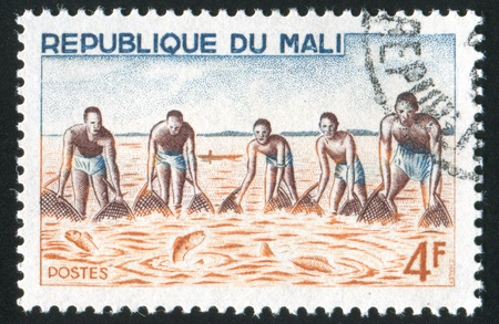 MALI CIRCA 1966: stamp printed by Mali, shows Group fishing with net, circa 1966 Stock Photo - 11893214