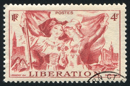 FRANCE - CIRCA 1945: stamp printed by France, shows Costumes of Alsace and Lorraine and Cathedrals of Strasbourg and Metz, circa 1945 photo