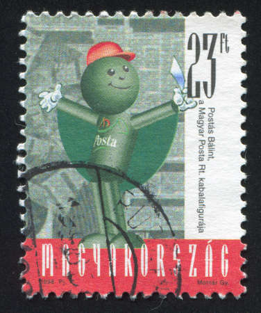 HUNGARY - CIRCA 1998: stamp printed by Hungary, shows Balint Postas (Post Office Mascot) Holding Letter in front of the Printed Material, circa 1998 photo