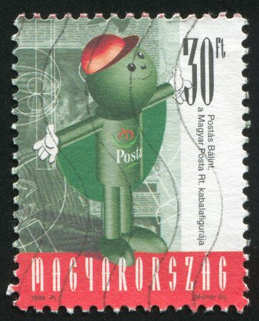 outstretched: HUNGARY - CIRCA 1998: stamp printed by Hungary, shows Balint Postas (Post Office Mascot) Staying Straight with Arms Outstretched in Front of the Printed Material, circa 1998