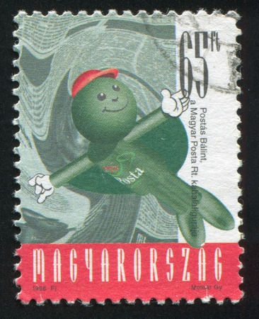 arms outstretched: HUNGARY - CIRCA 1998: stamp printed by Hungary, shows Balint Postas (Post Office Mascot) Staying Straight with Arms Outstretched in Front of the Printed Material, circa 1998