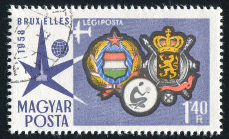 HUNGARY  CIRCA 1958: stamp printed by Hungary, shows emblem of Brussels and bending the kneemen, circa 1958 photo