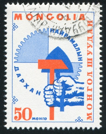 MONGOLIA — CIRCA 1968: stamp printed by Mongolia, shows tool in the hand in town of Darhan, circa 1968 photo