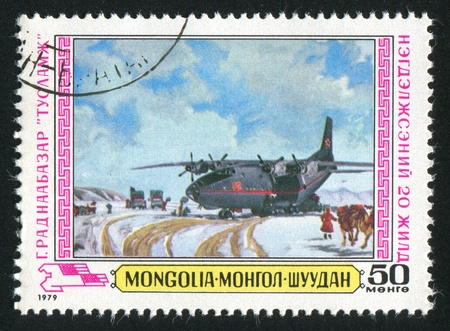 MONGOLIA - CIRCA 1979: stamp printed by Mongolia, shows plane bringing supplies in winter, circa 1979 photo