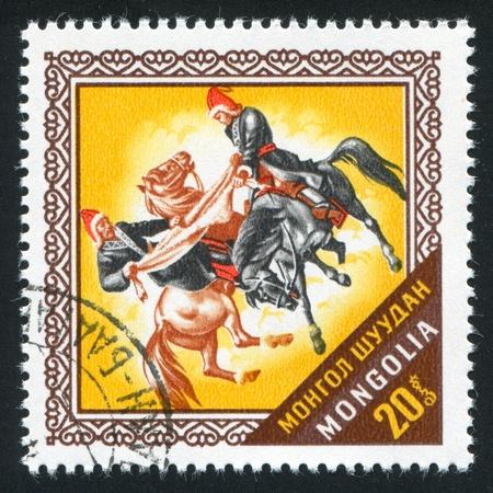 MONGOLIA - CIRCA 1974: stamp printed by Mongolia, shows Two horsemen fighting for goatskin, circa 1974 photo