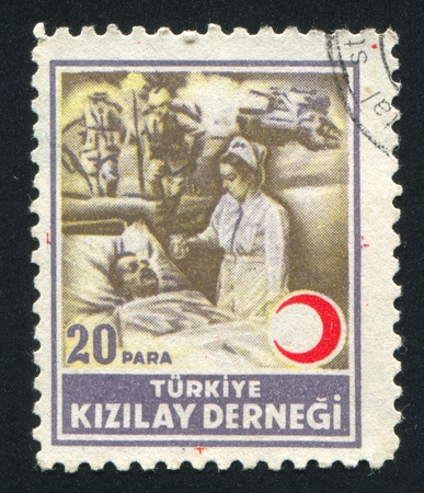 TURKEY- CIRCA 1944: stamp printed by Turkey, shows sister at the bedside, circa 1944 Stock Photo - 12999599