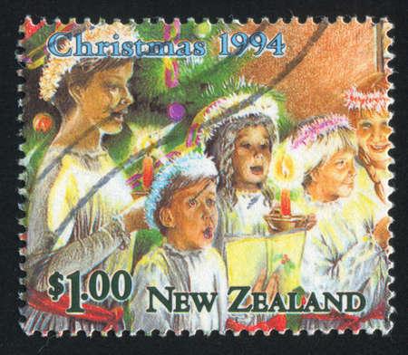 NEW ZEALAND - CIRCA 1994: stamp printed by New Zealand, shows sing carols near Christmas tree, circa 1994