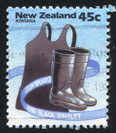 NEW ZEALAND - CIRCA 1994: stamp printed by New Zealand, shows Kiwiana, Black singlet and gumboots, circa 1994 Stock Photo - 13461064