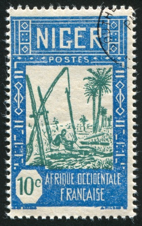 counterpoise: NIGER - CIRCA 1926-1940: stamp printed by Niger shows Drawing Water from Well, circa 1926-1940 Stock Photo