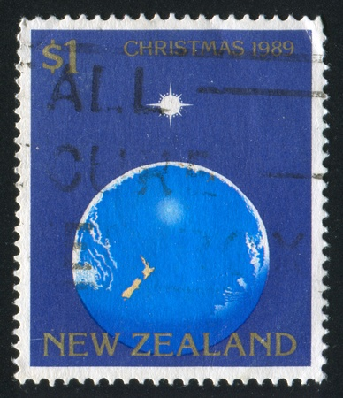 NEW ZEALAND - CIRCA 1989: stamp printed by New Zealand, shows Christmas, Star of Bethlehem illuminating settings, Earth, circa 1989 photo