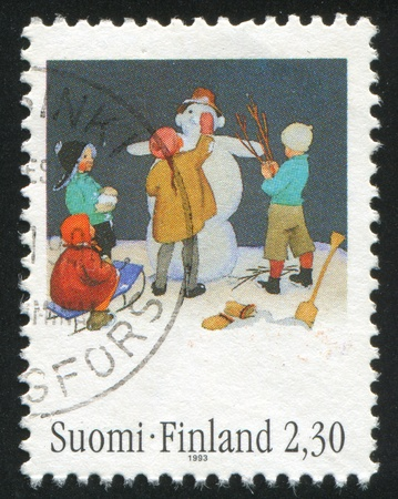 FINLAND - CIRCA 1993:  stamp printed by Finland, shows children in make snowman, circa 1993 photo