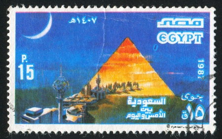EGYPT - CIRCA 1987: stamp printed by Egypt, shows Stylized pyramid, caravan, buildings, circa 1987 photo