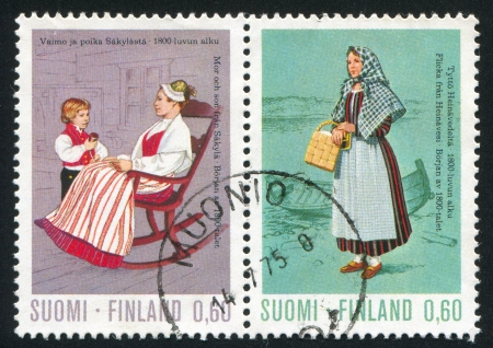 FINLAND - CIRCA 1973: stamp printed by Finland, shows Girl from Heinavesi and Mother and Son from Satakunta, circa 1973 photo