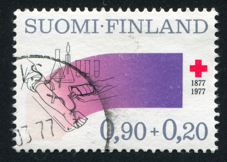 FINLAND - CIRCA 1977: stamp printed by Finland, shows Red cross, hand and dropping bottle, circa 1977 Stock Photo - 14145624