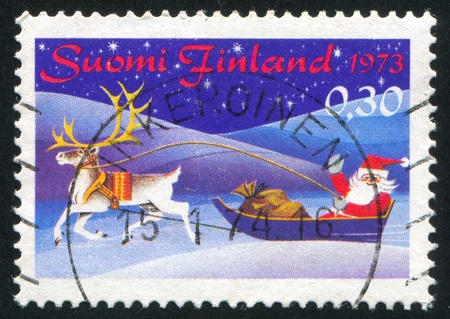 FINLAND - CIRCA 1973:  stamp printed by Finland, shows Santa Claus in reindeer sleigh, circa 1973 photo