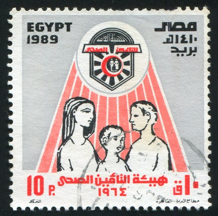 EGYPT - CIRCA 1989: stamp printed by Egypt, shows National Health insurance Emblem, Man, Woman, children, circa 1989 photo