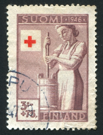 churning: FINLAND - CIRCA 1946: stamp printed by Finland, shows Farmers Wife Churning Butter, circa 1946 Editorial