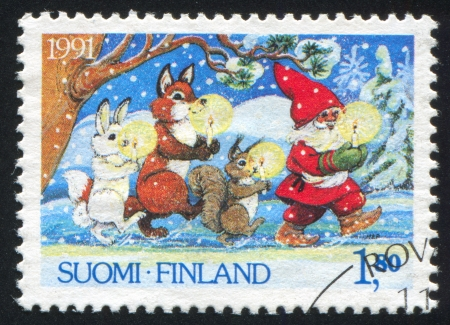 FINLAND - CIRCA 1991: stamp printed by Finland, shows Santa Claus and Animals Carrying Candles, circa 1991 Stock Photo - 14173147