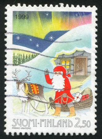 FINLAND - CIRCA 1999: stamp printed by Finland, shows Santa with his Sleigh, circa 1999 photo