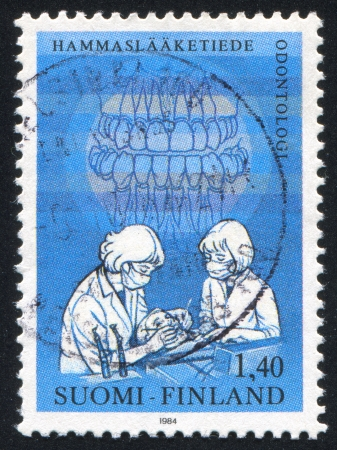 FINLAND - CIRCA 1984: stamp printed by Finland, shows Dentists Examining Patient, circa 1984 photo