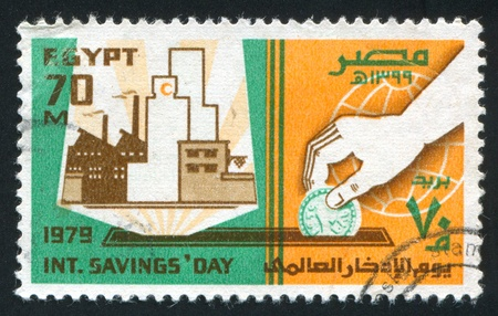 abjad: EGYPT - CIRCA 1979: stamp printed by Egypt, shows Hand with coin, factory, circa 1979 Editorial