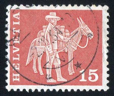 pack animal: SVIZZERA - CIRCA 1960: timbro stampato dalla Svizzera, mostra postino e pacco animali, circa 1960