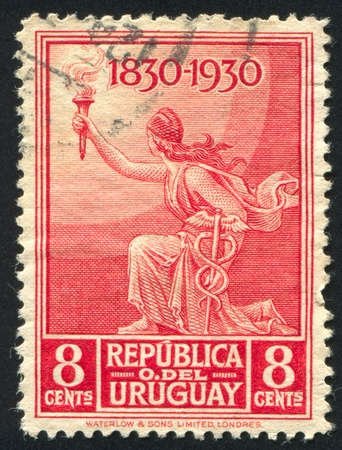 URUGUAY - CIRCA 1930: stamp printed by Uruguay, shows Liberty with Torch and Caduceus, circa 1930