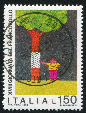auscultoscope: ITALY - CIRCA 1976: stamp printed by Italy, shows Boy healing tree by children drawing, circa 1976 Editorial