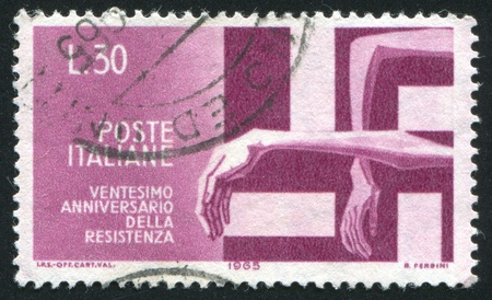 nazism: ITALY - CIRCA 1965: stamp printed by Italy, shows Victims trapped by Swastika, circa 1965