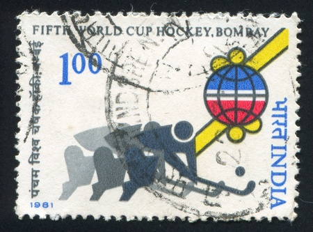 INDIA - CIRCA 1981: stamp printed by India, shows stylized Field hockey players and globe, circa 1981