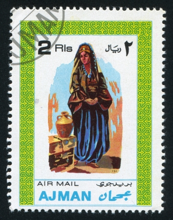 olla: AJMAN - CIRCA 1976: stamp printed by Ajman, shows a Woman and a Jar, circa 1976