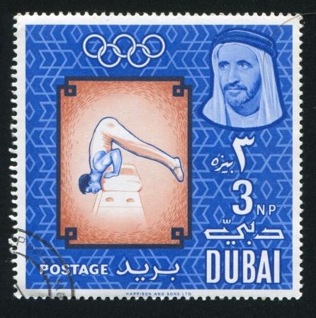 olympic ring: DUBAI - CIRCA 1982: stamp printed by Dubai, shows Mens Artistic gymnastics, circa 1982 Editorial