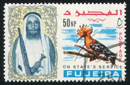 fujeira: FUJEIRA - CIRCA 1976: stamp printed by Fujeira, shows a Man and a Bird, circa 1976 Editorial